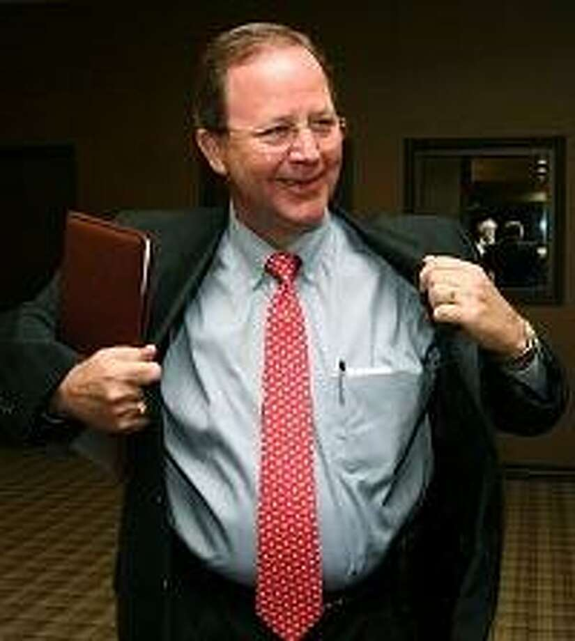 Republican Bill Flores puts on his coat before watching election results in Bryan.