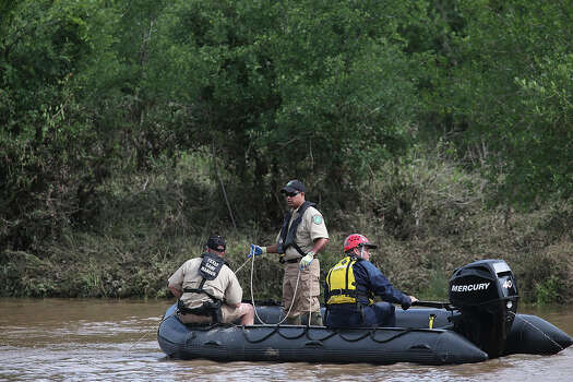 Emergency personnel search the Cibolo Creek for the body of 18-year-old Avron Adams, Sunday, May 26, 2013, Adam drowned when swimming the rain swollen creek on Saturday in Schertz. The body was recovered later in the afternoon. Photo: Jerry Lara, San Antonio Express-News / ©2013 San Antonio Express-News