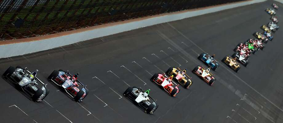 Tony Kanaan (far left) of Brazil leads the pack into the turn on his way to winning the 97th Indianapolis 500. Kanaan, who had led the third-most laps in history for a non-winner, had long been considered the best driver never to have won Indy. No more. Photo: Jonathan Ferrey, Getty Images