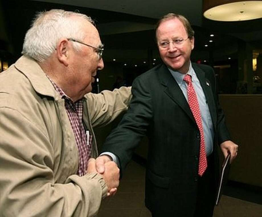 Republican Bill Flores, right, shakes hands with Alan Waldie, left, before watching election results in Bryan,