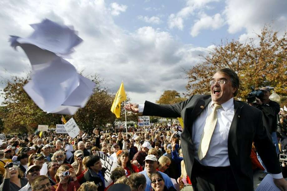 Rep. John Culberson, R-Texas throws the Health Care bill to the crowd on Capitol Hill in Washington, Thursday, Nov. 5, 2009, during a health care reform  rally.  (AP Photo/Jose Luis Magana) Photo: Jose Luis Magana, AP / FR159526 AP