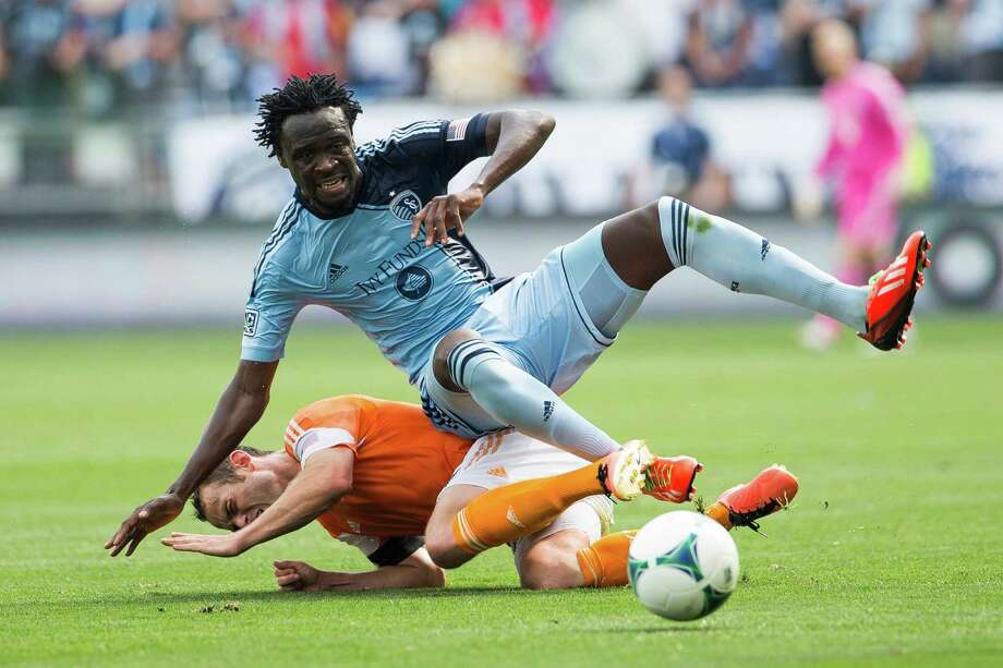 Brad Davis #11 of the Houston Dynamo slide tackles Kei Kamara #23 of Sporting KC on Sunday, May 26, 2013, at Sporting Park in Kansas City, Kansas.  Sporting KC and the Houston Dynamo tied 1-1 Photo: Brian Davidson / Brian Davidson / Special to the Kansas City Star