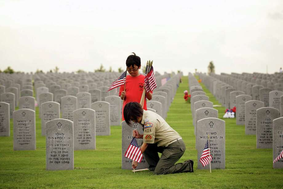 Preparing for Memorial Day ceremonies on Monday, volunteers Tho Miller, and her son Brandon, 10, of Boy Scout troop 414, place flags at a gravesite. They were part of  Flags for Fallen Vets, a Sunday project at the Houston National Cemetery on Veterans Memorial Drive. A U.S. flag was placed at every grave in the cemetery. Photo: Â TODD SPOTH, 2013 / © TODD SPOTH, 2013