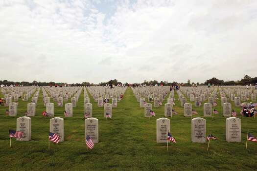 Like troops lined up in ranks, rows of gravestones at Houston National Cemetery extend into the distance, each with a U.S. flag placed Sunday by Flags for Fallen Vets. Photo: Â TODD SPOTH, 2013 / © TODD SPOTH, 2013