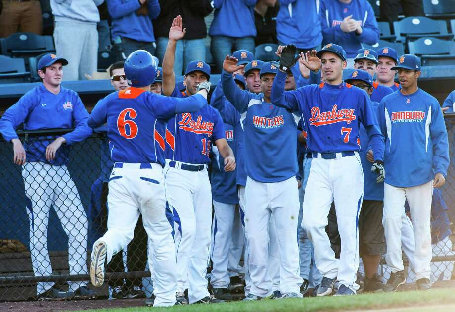 Danbury high school teammates congratulate Nicholas Goetz after Goetz scores a run in the FCIAC baseball championship game against Trumbull high school played at The Ballpark at Harbor Yard, Bridgeport, CT on Sunday May 26th, 2013. Photo: Mark Conrad / Connecticut Post Freelance