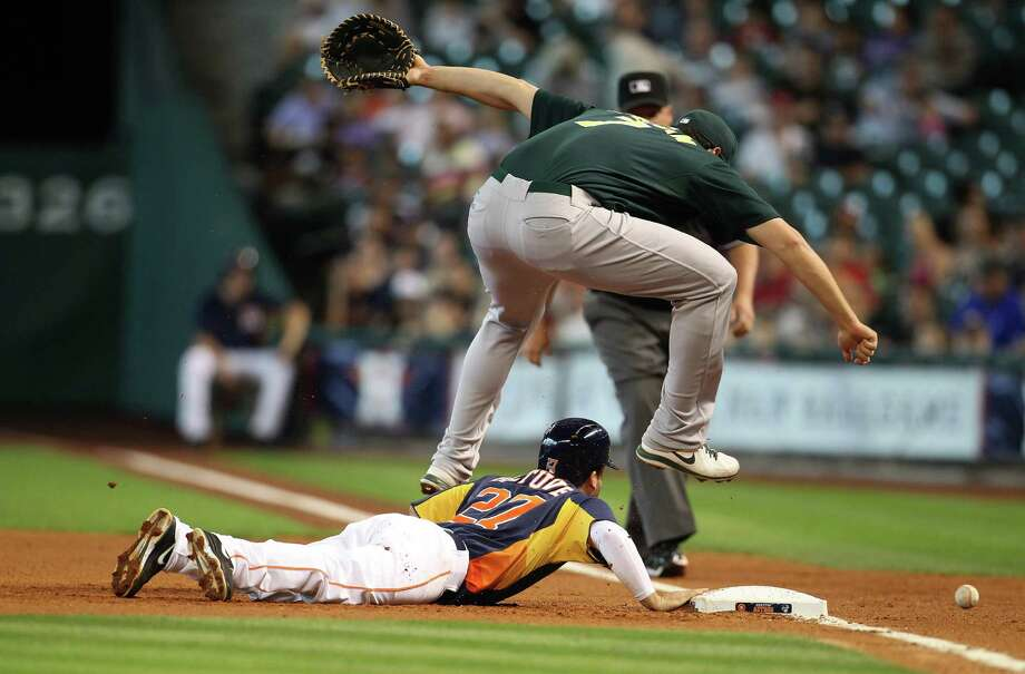 Showing some Oakland athleticism, A's first baseman Nate Freiman vaults the Astros' Jose Altuve to retrieve an errant pickoff throw by Bartolo Colon in Sunday's first inning. Freiman got the ball in time to prevent Altuve from advancing. Photo: Karen Warren, Staff / © 2013 Houston Chronicle