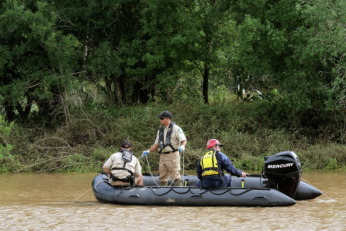 Emergency personnel search the Cibolo Creek for the body of 18-year-old Avron Adams, Sunday, May 26, 2013, Adam drowned when swimming the rain swollen creek on Saturday in Schertz.