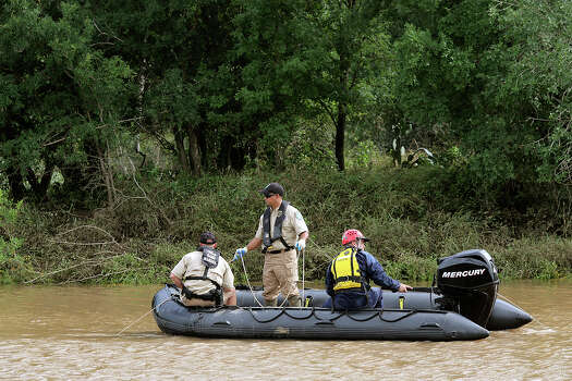 Emergency personnel search the Cibolo Creek for the body of 18-year-old Avron Adams, Sunday, May 26, 2013, Adam drowned when swimming the rain swollen creek on Saturday in Schertz. Photo: San Antonio Express-News / ©2013 San Antonio Express-News