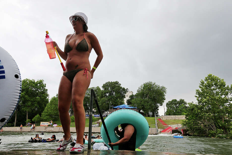 With a cloud of rain looming in the background, Crsytal Salts, 22, of Dallas exits the Comal River at Prince Solms Park in New Braunfels, Sunday, May 26, 2013. The Memorial Day weekend marks the start of tubing on the Comal and Guadalupe Rivers. Photo: San Antonio Express-News / ©2013 San Antonio Express-News