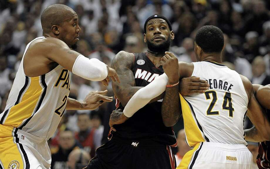 David West and Paul George do their best to strong-arm LeBron James, who led the Heat with 22 points. Photo: Michael Laughlin, MBR / Sun Sentinel