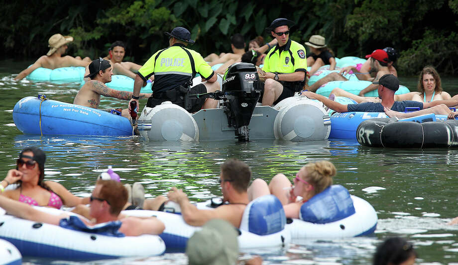 In this file photo, New Braunfels Police officers empty a glass container found on a tuber on Comal River by Prince Solms Park. Photo: San Antonio Express-News / ©2013 San Antonio Express-News