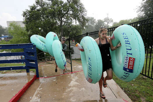 Caytlin Holland, 24, and Justin Stanely, 30, both of San Antonio, leave the Comal River at Prince Solms Park in New Braunfels, Sunday, May 26, 2013. The Memorial Day weekend marks the start of tubing season on the Comal and Guadalupe Rivers. Photo: San Antonio Express-News / ©2013 San Antonio Express-News