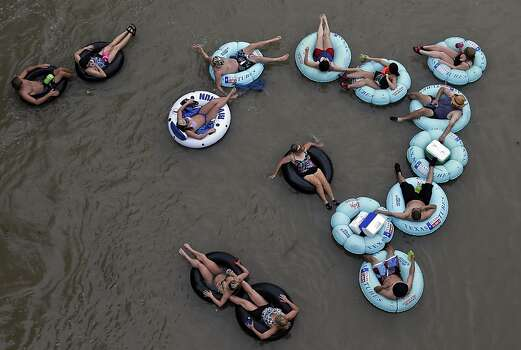 Tubers float the Comal River, Sunday, May 26, 2013, in New Braunfels, Texas. The rivers in New Braunfels were open to tubing Sunday despite Saturday's heavy rainfall.  (AP Photo/Eric Gay) Photo: Eric Gay, Associated Press