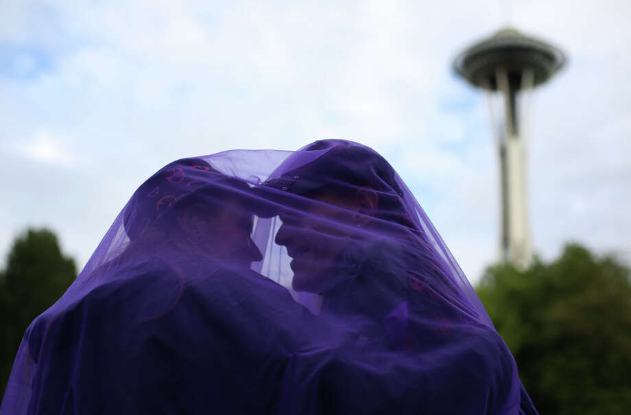 Tammy Melugin and Chris Williams look for some privacy under purple fabric during the Northwest Folklife Festival. Photo: JOSHUA TRUJILLO, SEATTLEPI.COM / SEATTLEPI.COM