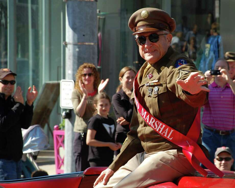 Leonard Everett Fisher, a World War II veteran and grand marshal of the Memorial Day parade, draws cheers as he is driven through downtown Monday morning.   WESTPORT NEWS, CT 5/27/13 Photo: Jarret Liotta / Westport News contributed