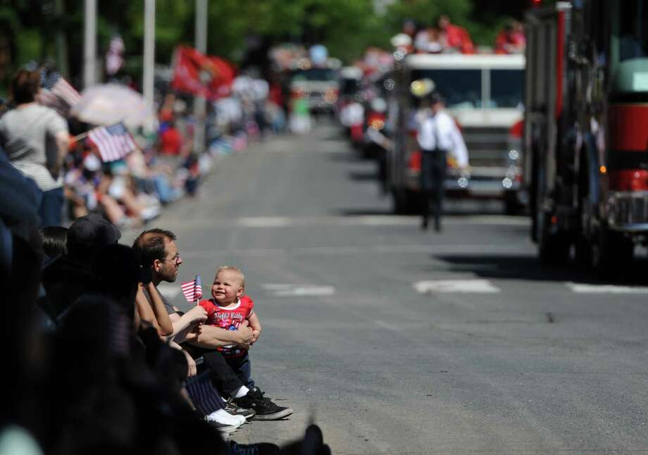 Adam Rushka, of Bethel, and his duaghter Madelynn, 1, watch the Danbury Memorial Day parade on Main Street in Danbury, Conn. on Monday, May 27, 2013.  The parade began at Rose Street and Main Street, finishing at Rogers Park, where skydivers dropped onto the field at Rogers Park Middle School.  The parade was followed by a memorial service at the Rogers Park Rose Memorial Garden. Photo: Tyler Sizemore / The News-Times