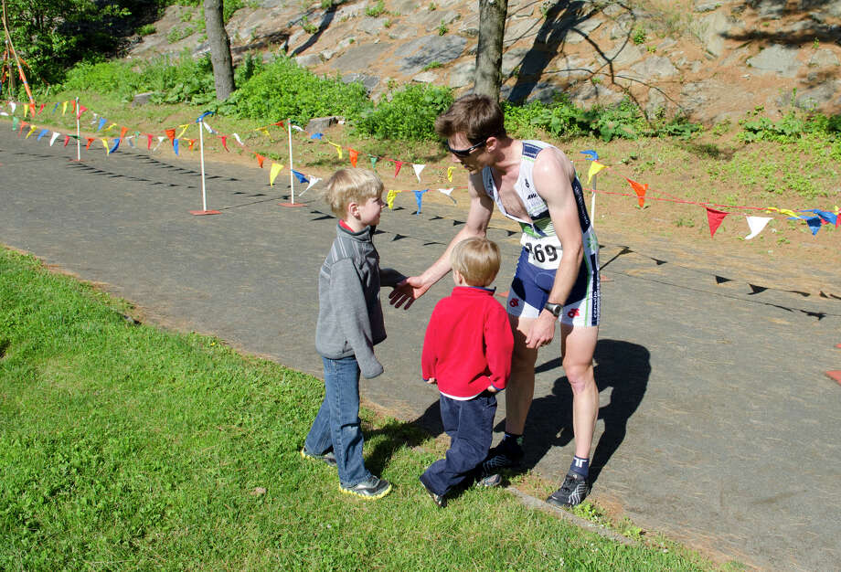 Eneas Freyre, 36, Norwalk, 27:08, greets his sons Caden, 6, and Rhys, 3, at the conclusion of the annual Jim Fixx Run, a five-mile road race, in Greenwich on Monday, May 27, 2013. Photo: Amy Mortensen / Connecticut Post Freelance