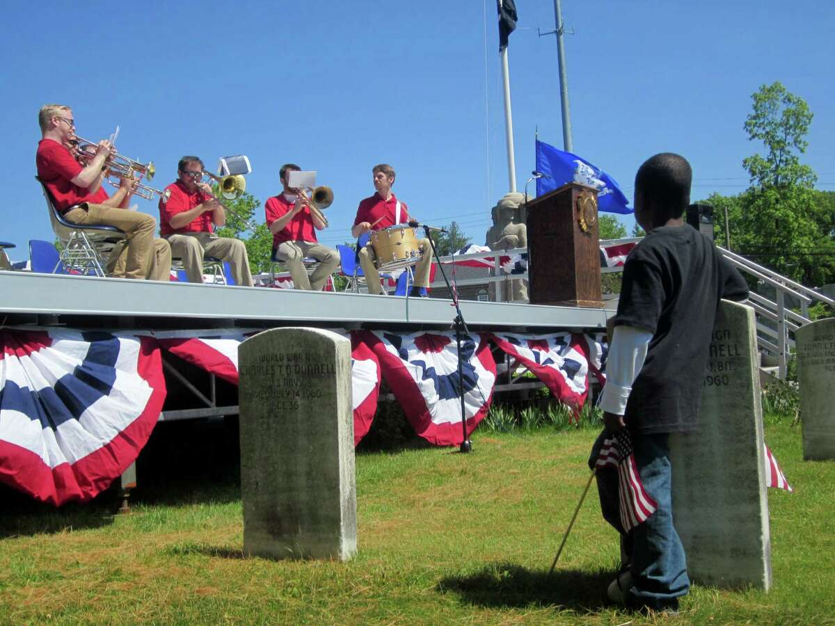 A young boy looks on while the band plays patriotic songs and armed forces themes in the Spring Grove Cemetary on Memorial Day.
