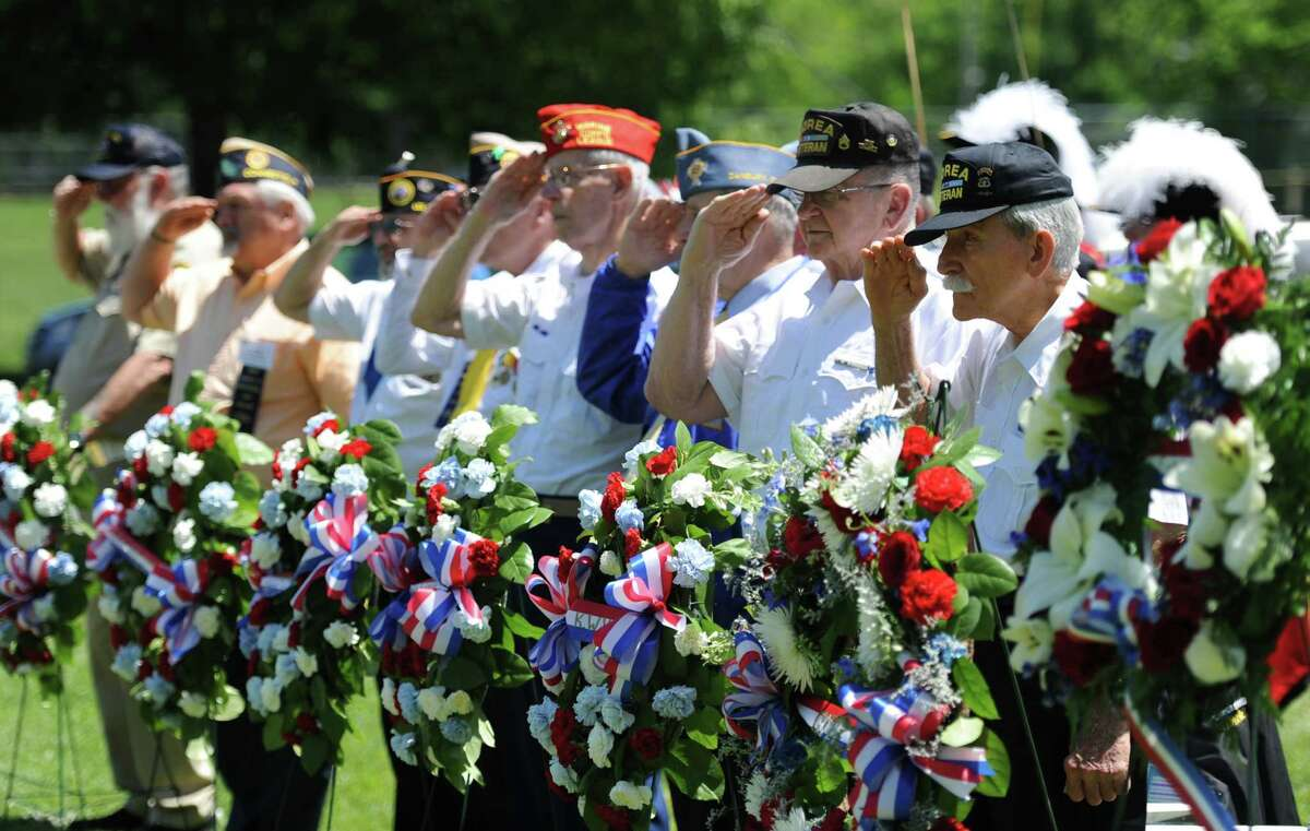 War veterans salute as the names of deceased veterans are read aloud during the Memorial Day service at the Rogers Park Rose Memorial Garden on Monday, May 27, 2013.