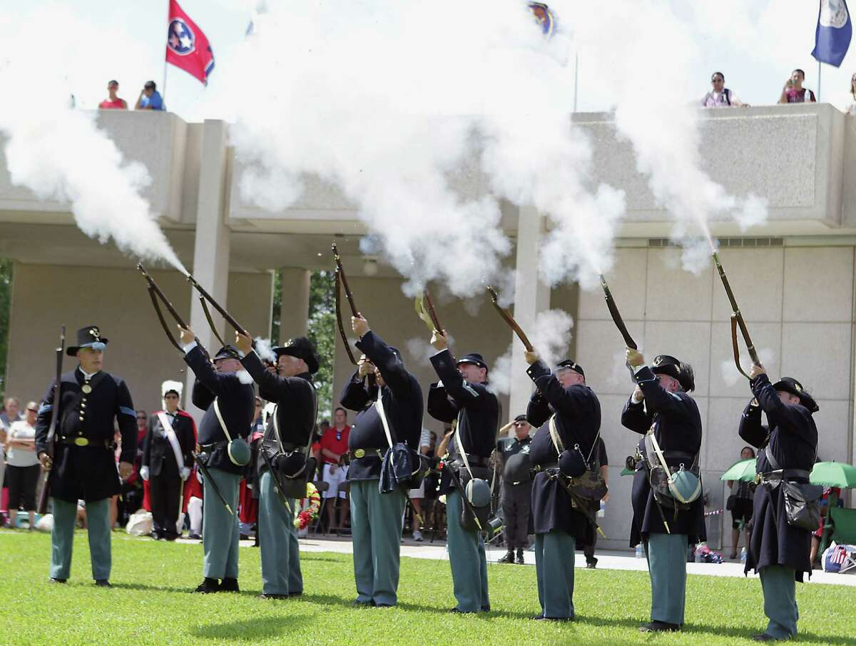 Members of the 15th Texas Infantry (Confederate) fire during rifle salute at the Houston National Cemetery Memorial Day Service Monday, May 27, 2013, in Houston.
