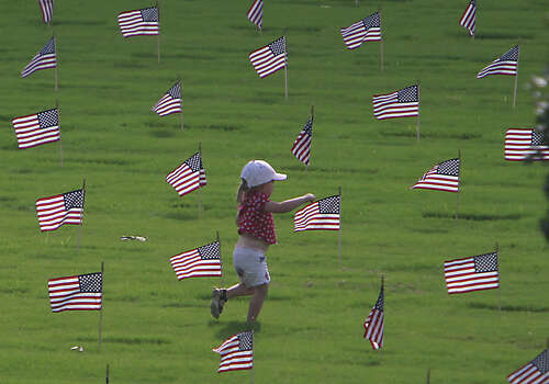 A young child runs amongst the grave sites during the Houston National Cemetery Memorial Day Service Monday, May 27, 2013, in Houston. Photo: James Nielsen, Houston Chronicle / © 2013  Houston Chronicle