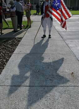 US Army veteran Tom Boone wight he Heroes of 76 holds a flag prior to the Houston National Cemetery Memorial Day Service Monday, May 27, 2013, in Houston. Photo: James Nielsen, Houston Chronicle / © 2013  Houston Chronicle