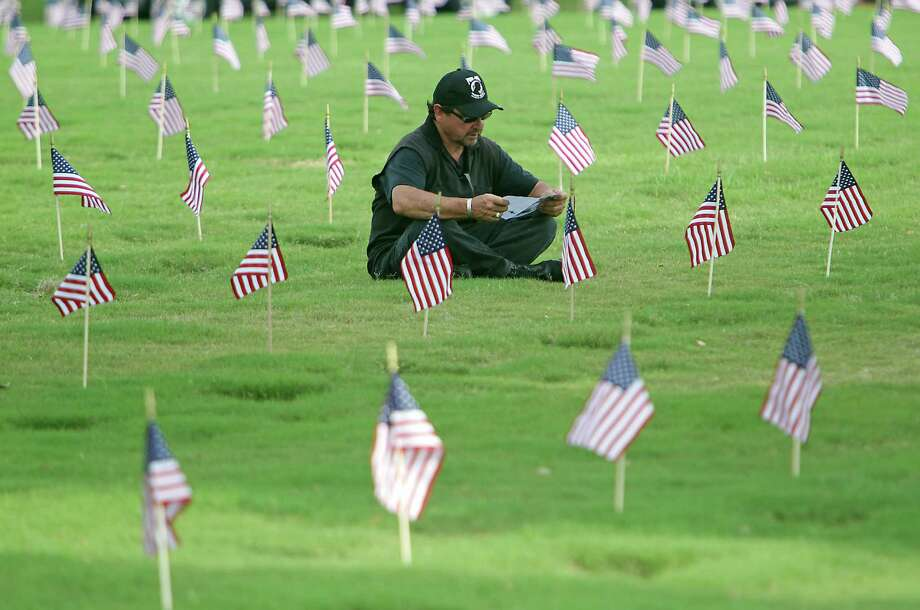 Rudy Montez looks over the program while sitting amongst  grave sites prior to the Houston National Cemetery Memorial Day Service Monday, May 27, 2013, in Houston. Montez has family and friends buried in the cemetery. Photo: James Nielsen, Houston Chronicle / © 2013  Houston Chronicle