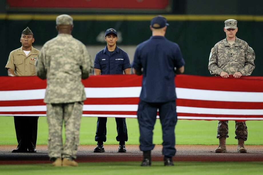 Members of the armed services hold a giant American Flag  during pre-game ceremonies before the start of an MLB game at Minute Maid Park, Monday, May 27, 2013, in Houston. Photo: Karen Warren, Houston Chronicle / © 2013 Houston Chronicle