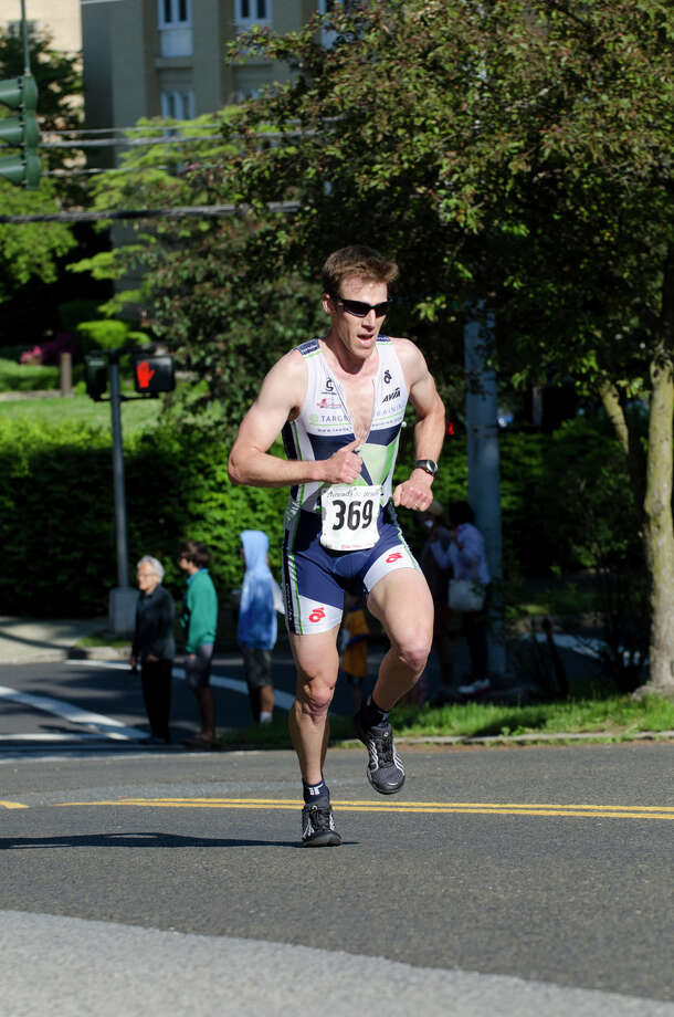 Eneas Freyre, 36, Norwalk, 27:08, races through downtown Greenwich during the annual Jim Fixx Run, a five-mile road race, in Greenwich on Monday, May 27, 2013. Photo: Amy Mortensen / Connecticut Post Freelance