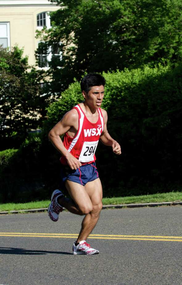 Alejandro Ariza, 23, Brooklyn, NY, 27:00, races through Greenwich during the annual Jim Fixx Run, a five-mile road race, in Greenwich on Monday, May 27, 2013. Photo: Amy Mortensen / Connecticut Post Freelance