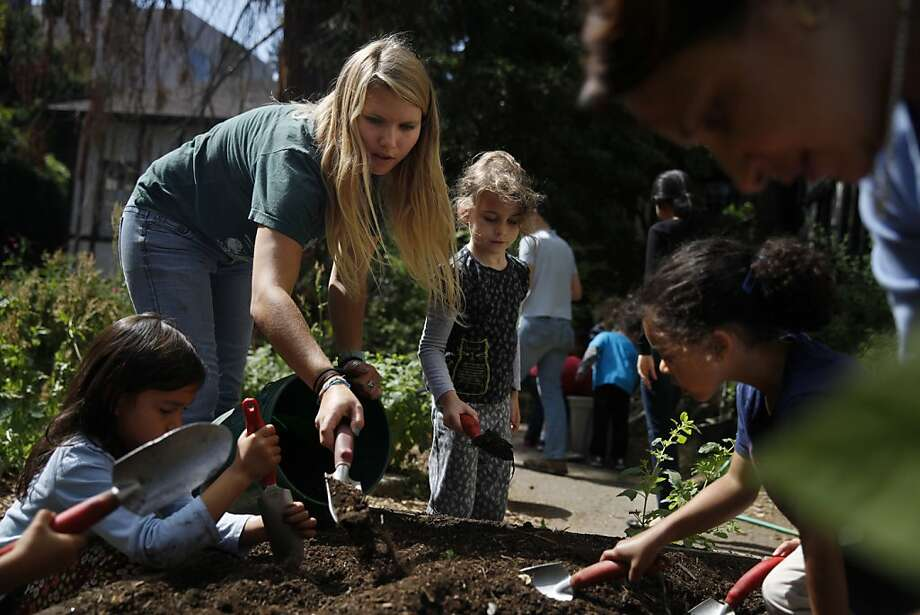 Volunteer Jenny Wood shows members of a prekindergarten High Five class how to mix compost into soil in the garden at John Muir Elementary School in Berkeley. Photo: Lea Suzuki, The Chronicle