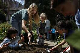 Jenny Wood (second from left), volunteer, shows High Five students how to mix compost with soil during class in the garden at John Muir Elementary School on Friday, May 17, 2013 in Berkeley, Calif.