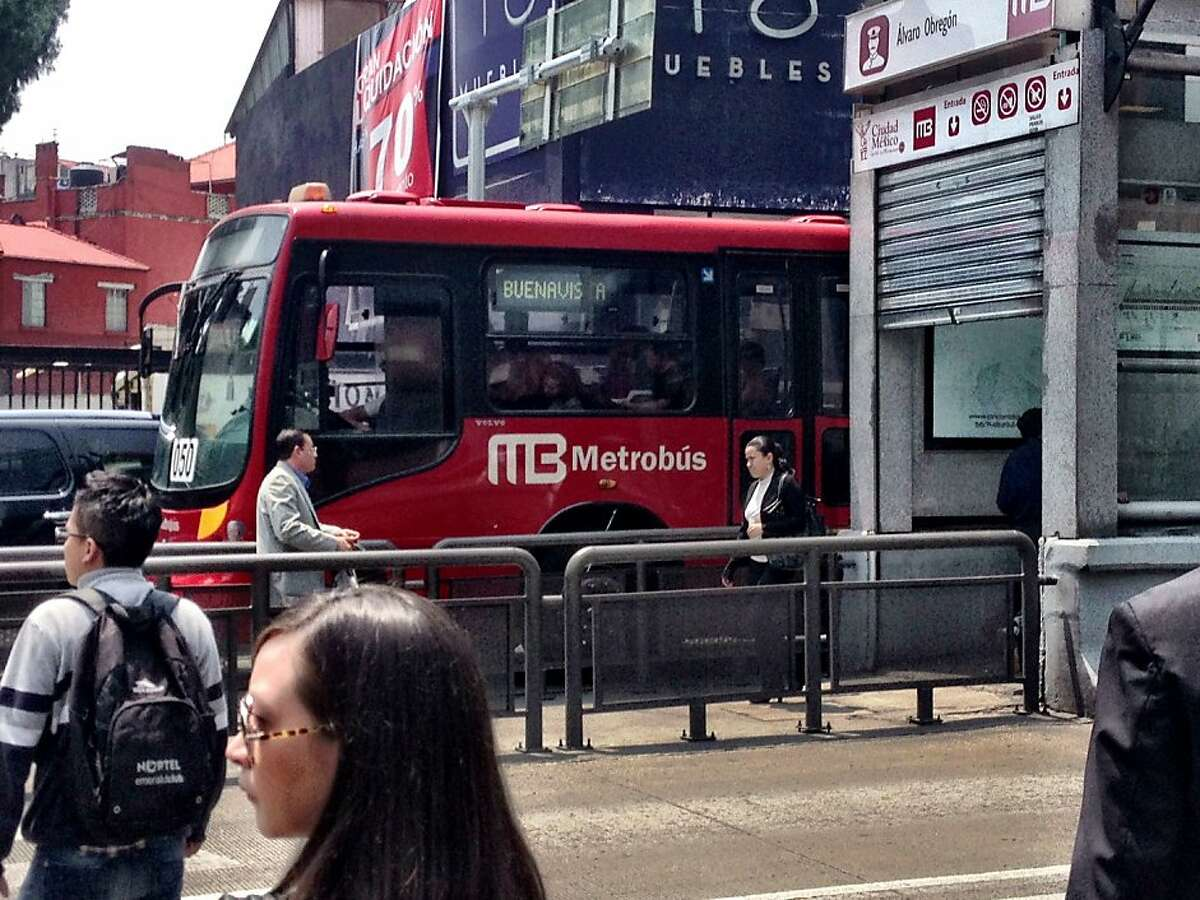 A Mexico City Metrobus pulls out of a station.