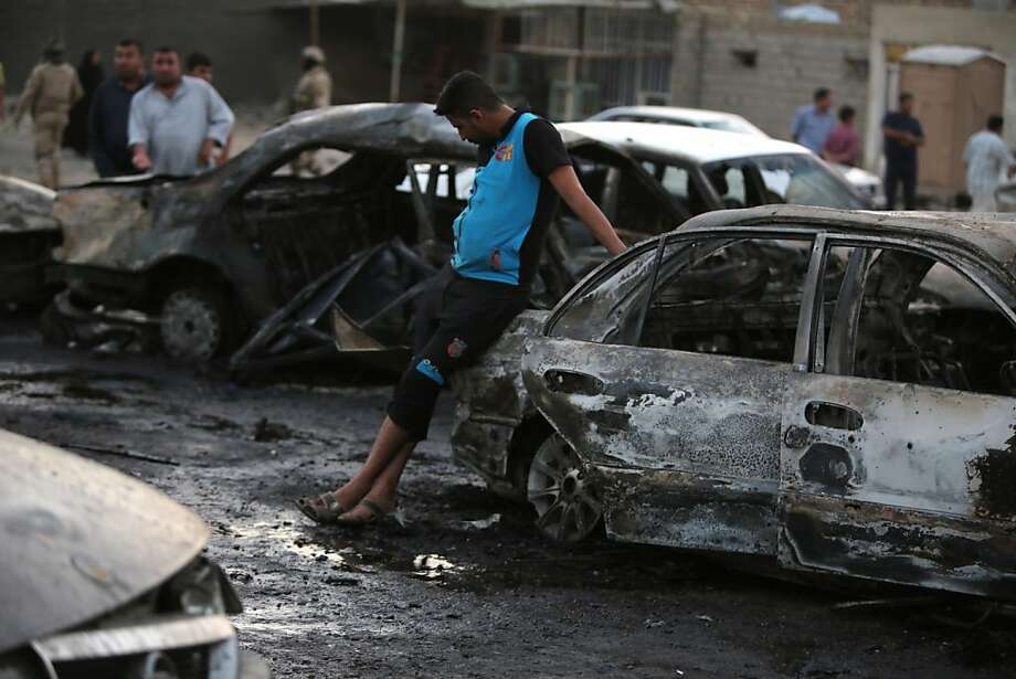 Men gather at the scene of a car bomb that exploded in Baghdad's Habibiya area. More than 450 people have been killed across Iraq in May in the bloodiest wave since U.S. troops left in 2011. Photo: Ahmad Al-rubaye, AFP/Getty Images