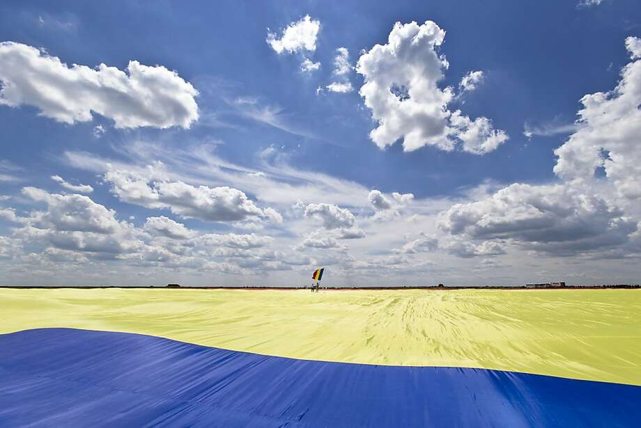 A man holding a Romanian flag stands on a record breaking version of the flag, on the Clinceni Airfield, south of Bucharest,  Romania, Monday, May 27, 2013. Romania entered the Guinness Book of records after it unveiled the largest flag ever made. It took about 200 people several hours Monday to unfurl a five-ton flag of Romania which organizers said measured 349.4 meters by 226.9 meters, about three times the size of a football pitch.(AP Photo/Vadim Ghirda) Photo: Vadim Ghirda, Associated Press