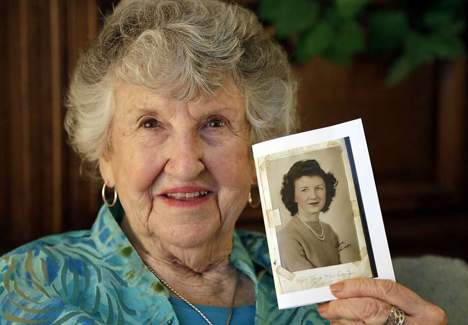 "Laura Mae Davis Burlingame, 90, holds the photo of herself that filled the back cover of a diary she had given to a Marine Cpl. Thomas ""Cotton"" Jones. Photo: Michael Conroy, Associated Press"
