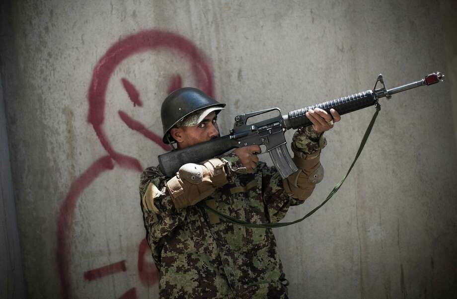 An Afghan soldier takes position during a house-to-house search at a training facility near Kabul, Afghanistan. In roughly 90 percent of the country, Afghan police and soldiers take the fight to the Taliban alone. Photo: Anja Niedringhaus, STF / AP
