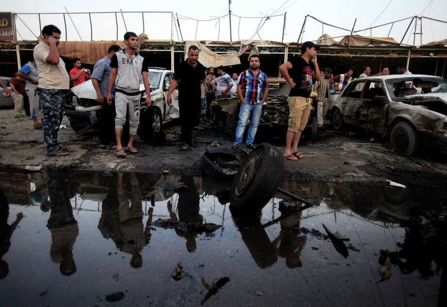 Iraqis view the scene of a car bomb attack at a used cars dealership in eastern Baghdad on Monday.  Photo: Karim Kadim, STF / AP