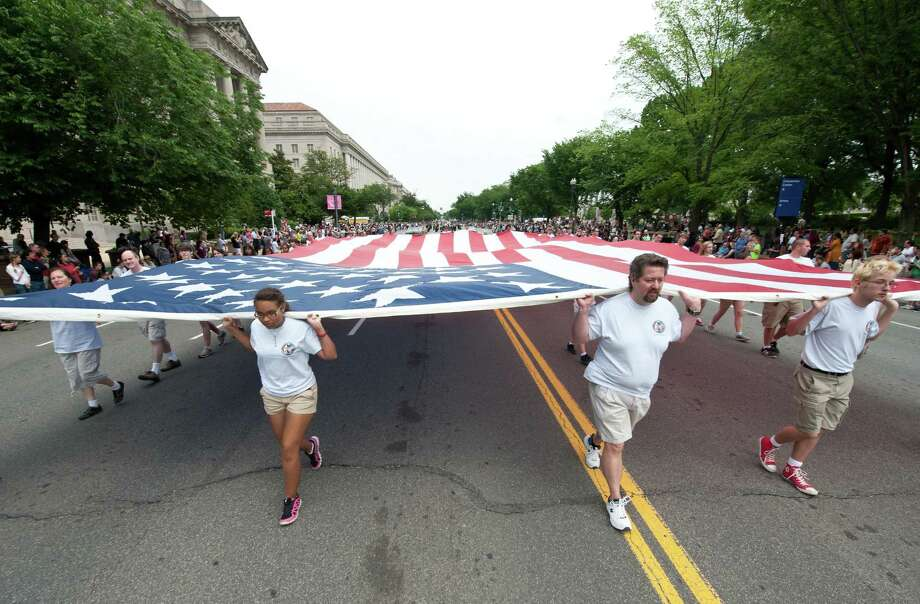 Participants carry a giant US flag during a Memorial Day parade in Washington on May 27, 2013. Memorial Day is a day of remembering the men and women who died while serving in the United States Armed Forces. Photo: Getty Images