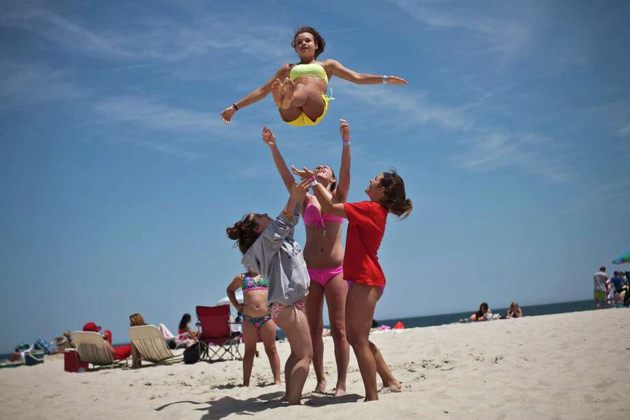 Emilie Sullivan is thrown into the air by her friends as they play on the first weekend of Jersey Shore beaches re-opening to the public on May 27, 2013 in Seaside Heights, New Jersey. The region continues to recover and rebuild after Hurricane Sandy devastated parts of the coastline. Photo: Kena Betancur, Getty Images / 2013 Getty Images