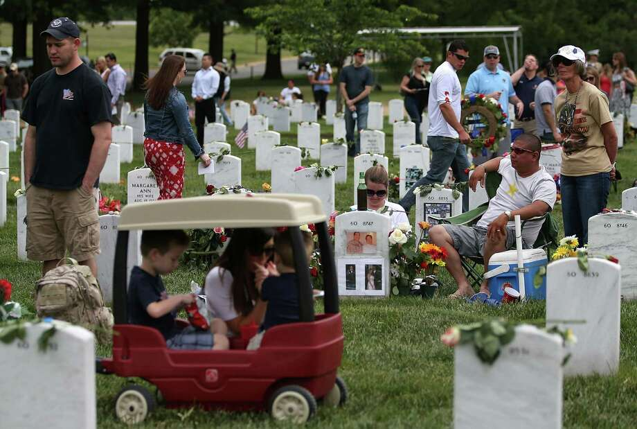 Friends and family visit gravesites in section 60 at Arlington Cemetery, May 27, 2013 in Arlington, Virginia. For Memorial Day President Obama layed a wreath at the Tomb of the Unknowns, paying tribute to military veterans past and present who have served and sacrificed their lives for their country. Photo: Mark Wilson, Getty Images / 2013 Getty Images