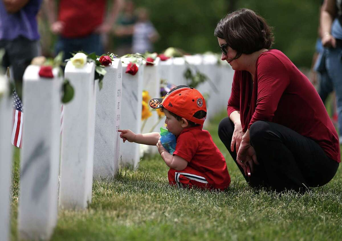 Anne Kornblut and her two-year-old son visit a gravesite in section 60 at Arlington Cemetery, May 27, 2013 in Arlington, Virginia. For Memorial Day President Obama layed a wreath at the Tomb of the Unknowns, paying tribute to military veterans past and present who have served and sacrificed their lives for their country.