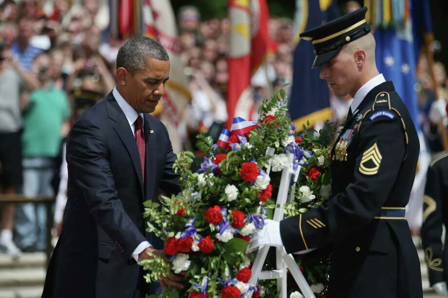 President Barack Obama positions a commemorative wreath during a ceremony on Memorial Day at the Tomb of the Unknowns at Arlington National Cemetery on May 27, 2013 in Arlington, Virginia. For Memorial Day President Obama is paying tribute to military veterans past and present who have served and sacrificed their lives for their country. Photo: Mark Wilson, Getty Images / 2013 Getty Images