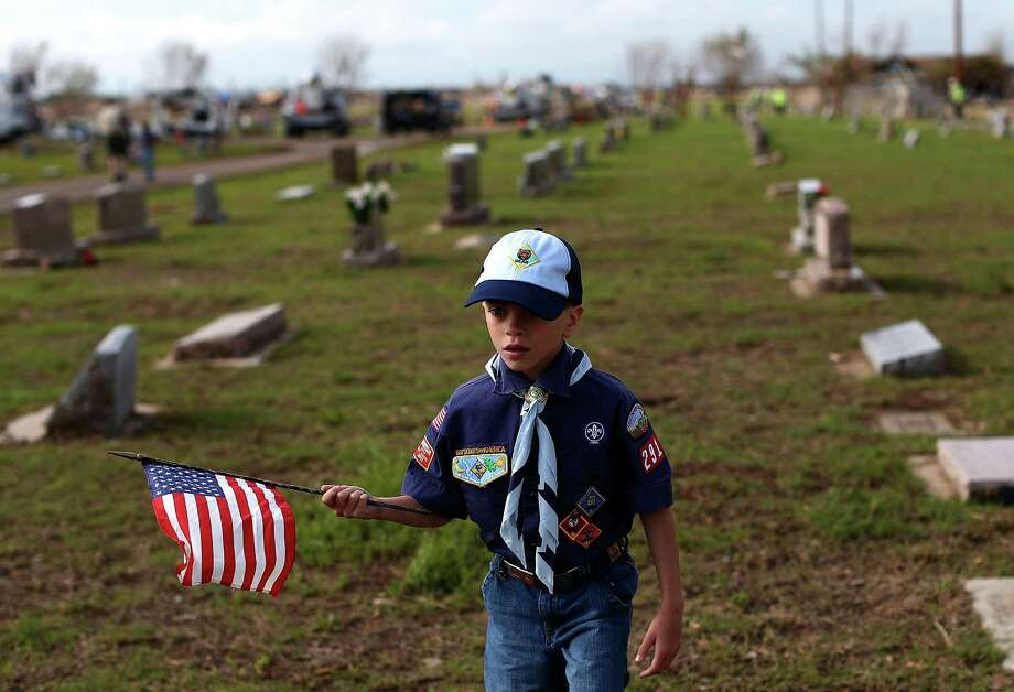 Cub Scout Owen Thomason waves American flags while placing a flag on the graves of veterans buried at Moore Cemetery on May 25, 2013 in Moore, Oklahoma. The annual Memorial Day project took place in the Moore Cemetery, which sits next to a tornado destroyed neighborhood. The tornado of EF5 strength and two miles wide touched down May 20 killing at least 24 people and leaving behind extensive damage to homes and businesses. U.S. President Barack Obama promised federal aid to supplement state and local recovery efforts. Photo: Tom Pennington, Getty Images / 2013 Getty Images