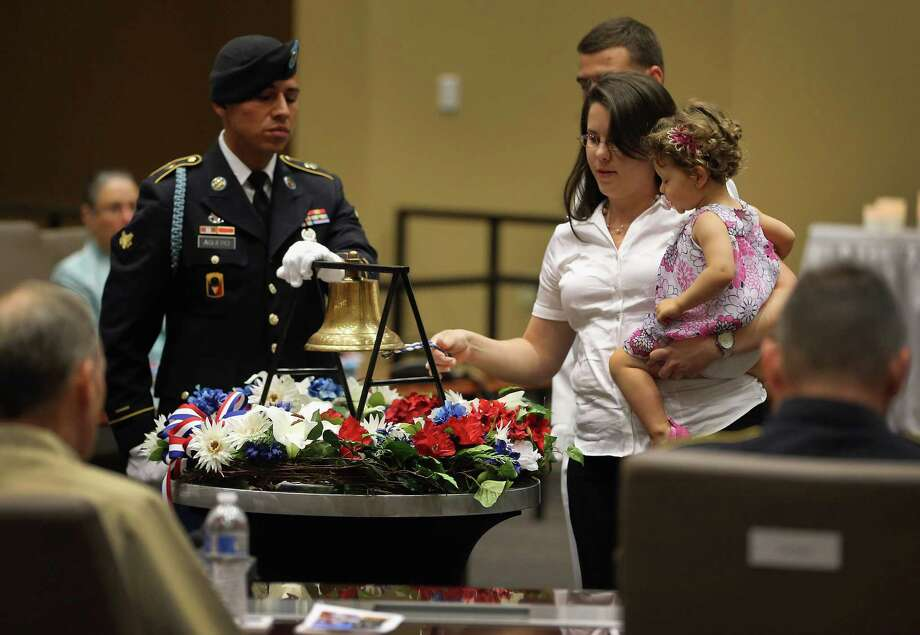 U.S. Army Specialist Juan Aguero, from the Florida National Guard Honor Guard, stands beside a bell as Joanna Gonzalez holds her daughter, Ayeleth Garces while ringing the bell in honor of her husband during a ceremony to remember and honor those who have died in service to the nation and the families they have left behind at  U.S. Southern Command headquarters on May 20, 2013 in Doral, Florida. U.S. Marine Gen. John Kelly presided over the ceremony where the families of 57 fallen service members from South Florida were invited to attend. Photo: Joe Raedle, Getty Images / 2013 Getty Images