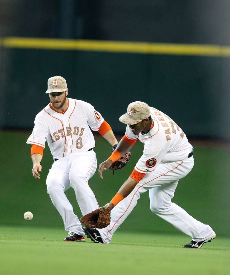 Astros outfielders Trevor Crowe and Jimmy Paredes try to track down a ball.