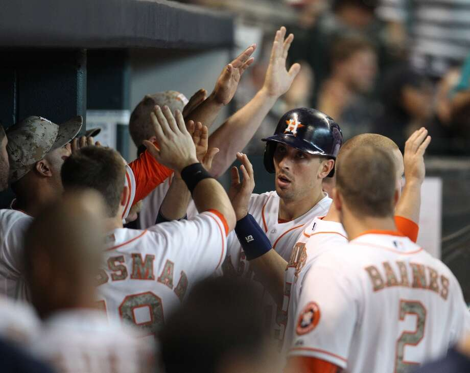 Jason Castro of the Astros is congratulated by teammates after scoring a run.