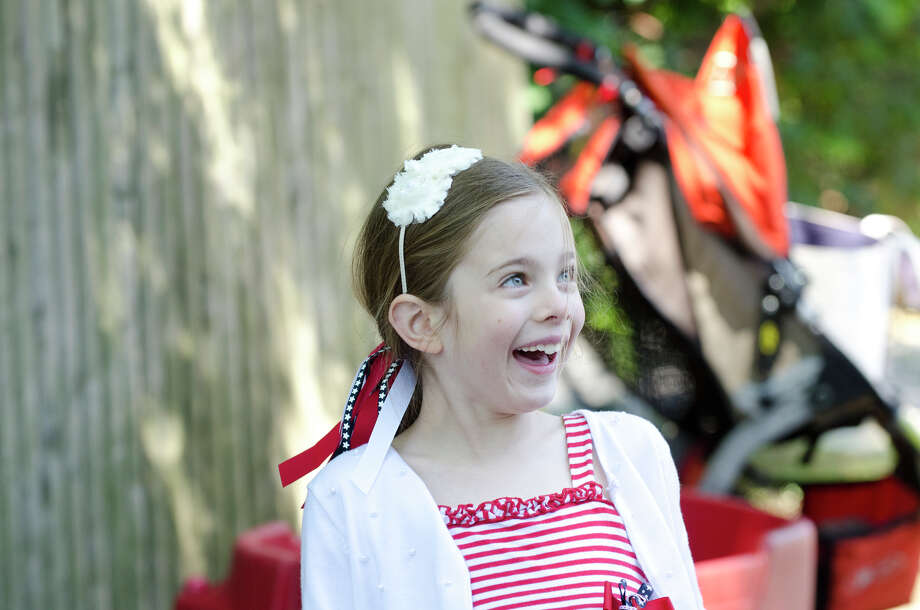 Alyssa Johnson, 7, of Greenwich, smiles during the Memorial Day parade on Sound Beach Avenue in Old Greenwich on Monday, May 27, 2013. Photo: Amy Mortensen / Connecticut Post Freelance