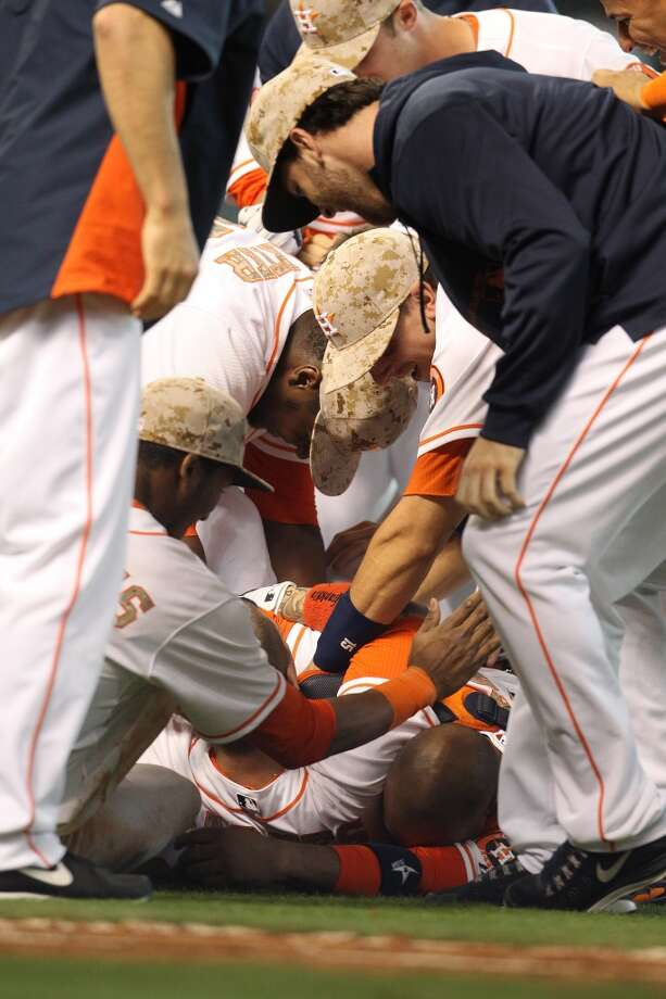 Astros right fielder Brandon Barnes gets pummeled by teammates after he hit a ground rule double to win the game in the 12th inning.