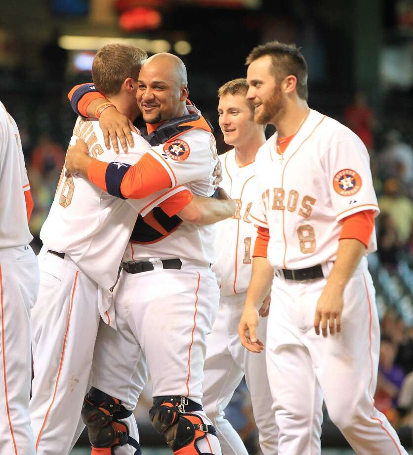 Astros catcher Carlos Corporan hugs relief pitcher Paul Clemens after right fielder Brandon Barnes' ground rule double scored the winning run.